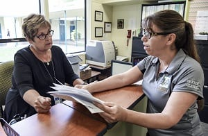 Woman assisting another woman with paperwork at an office
