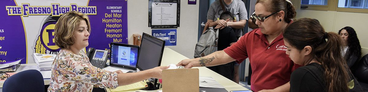 In a Fresno Unified administrative office, an employee hands some paperwork to another person.