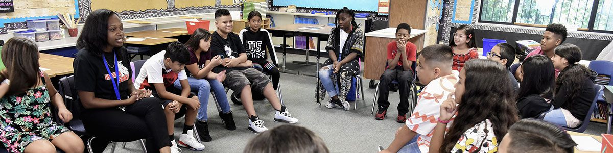 Students sitting in a circle in a classroom, listening to their teacher