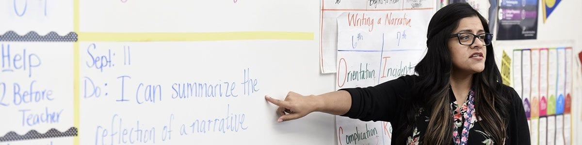 A Fresno Unified teacher pointing at a sentence written on a whiteboard.