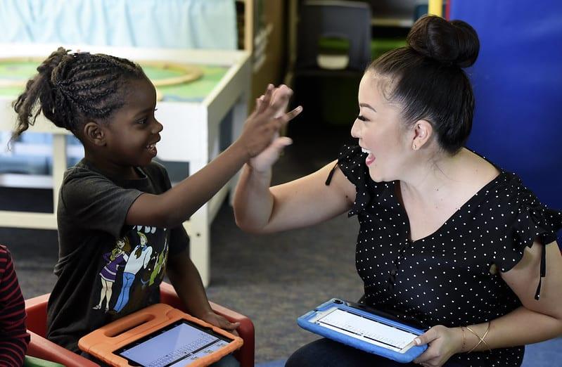 A teacher high-fives a young female student